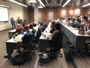 Different angle of Photo of a classroom of people sitting at rows of desks for an ExplOrigins meeting